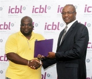 (IMAGE VIA - barbadosadvocate.com) Accepting the sum of five hundred dollars to be deposited on to his Registered Retirement Savings Plan (RRSP), from Senior VP – Life Division, ICBL, Henry Inniss was November winner David Green.