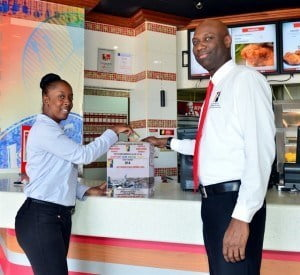 Chairman of Drug Education and Counselling Services (DECS), Roger Husbands, accepting a donation from KFC Marketing Coordinator, Shekelia Barrow during their recent meeting at KFC Warrens.