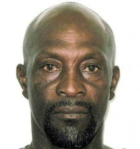 """Anthony is 5' 8"""" in height, muscular build and of a dark complexion.  He has an oval face, a small bald head, thin eyebrows, small dark brown eyes and a scar under his right eye.  He has a small moustache and a low beard."""