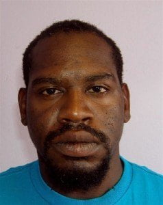 """He is Jason Cecil Spencer, 33 years of 4th Avenue Pickwick Gap, Westbury Road, St. Michael. He is about 5' 5"""" in height, medium build and of black complexion. He has black hair, dark brown eyes, large ears, a broad nose and thick lips. He has tattoos of a dollar bill on his right hand, and a skull on his right upper arm."""
