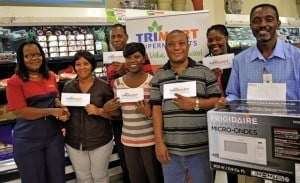 Karen Walcott (left), Trimart's Store Departmental Supervisor, congratulates (from left) Kerry-Ann Riley, Allan Haynes, Vesta Alleyne, Brantley Hunte, Tamorra Vanderpool and Nigel Hackett, winners of the 'Put Trimart in Your Cart this Christmas' promotion.