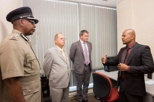 Mr. Ricky Nandlal - IT Administrator Police Complaints Authority (right) explains the use of the equipment to Ag Commissioner of Police Stephen Williams, (left), Canadian High Commissioner H.E. Gérard Latulippe (second from left) and Mr. Charles Moore, Chargé d'Affairs, British High Commission (second from right).