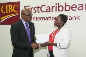 Michelle Whitelaw, Director, Retail Banking Channels, CIBC FirstCaribbean (right) presents Jerry Blenman, Executive Consultant and interim Chief Executive Officer, National Sports Council with funds to go towards awarding athletes at the recently-held NSC Annual Awards Ceremony 2014.