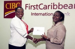 Michelle Whitelaw, Director, Retail Banking Channels, CIBC FirstCaribbean (left) presents Carolyn Lane, vice president of the Myasthenia Gravis Association of Barbados with funds for medical alert identity bracelets for persons living with the condition.