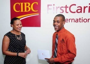 """Kemar Saffrey, President and Chairman of the Barbados Vagrants and Homeless Society (right) expresses pleasure at the $10,000 contribution from CIBC FirstCaribbean (represented here by Donna Wellington, Managing Director, Barbados) which he says will make a """"good impact""""."""