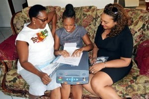 Visually impaired scholar, Janeil Odle (centre) using braille to read the instructions for her new Standalone Reading Appliance which was donated to her by Digicel (Barbados) Limited, represented her by Commercial Operations Director, Tanya Menzies-Beckford (right). Also, pictured is Janeil's mother, Heather.