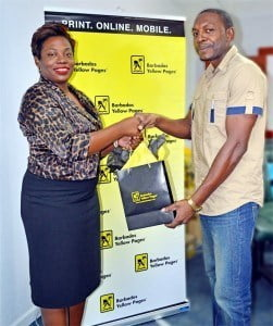At left Sabrina Greenidge Marketing Assistant - Barbados Yellow Pages shakes hands with grand prize winner of the Barbados Yellow Pages' Recycling Competition, Cecil King