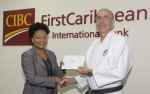Nicole Weekes, Senior Trust Officer, CIBC FirstCaribbean (left) presents Peter Warren, Chief Instructor, International Shotokan Karate Federation of Barbados (ISKF) with funds in support of its upcoming annual awards ceremony.