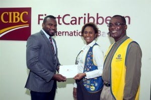 (l-r) Selwin Kellman, Portfolio Manager, Wealth Management, CIBC FirstCaribbean  presents Optimist Club of Barbados South members, Ann Sealy, treasurer; and Leo Brewster, president with funds for food hampers for families in need.