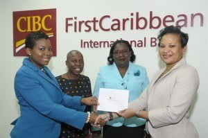 Donna Wellington, CIBC FirstCaribbean Barbados Country Head (right) presents Marianne Burnham, outgoing president of the Business and Professional Women's Club of Barbados (left) with $10,000 for the maintenance of security and safety of its shelter for women who are victims of domestic abuse. Witnessing the presentation are (from left) Marlene Hewitt, coordinator; and Jenifer Johnson, new president.