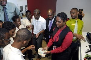 Irving Wilson School students along with their teacher, Kenneth Kinch (fourth from right) get a hands-on money lesson from Customer Service Officer, Lasonta Payne while Warrens Branch Manager, Richard Kennedy and Customer Service Representative, Decino Corbin (right) look on.