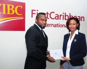 Selwin Kellman, Portfolio Manager, Wealth Management, CIBC FirstCaribbean presents Gillian Hassell, Managing Director of Aries Technology with funds to assist with the production of 11+ Challenge,  a new TV game show for schools.