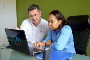 Managing Director of eCarib Marketing, Simone Stanford (right), shows Digicel Business Sales Manager, David Gilligan, some of the benefits her company has experienced thanks to the new cloud storage solution by Digicel Business
