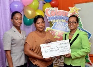 Esther La Cruz (centre) collects her winnings from Nicole Griffith of Harris Paints and Jennifer Cipriani of Scotiabank (right).