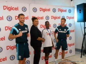 Cliff Gooding-Edghill (in the middle) basks in his moment of glory with Chelsea coaches book-ending and Digicel's Commercial Operations Manager, Tanya Menzies-Beckford