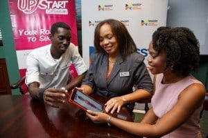 Israel Mallett of IDS Creative (left) and Heather Barker, communications consultant and founder of UPstart Caribbean (right) give Trudy Bellamy, Marketing Coordinator, Massy United Insurance a preview of a series of ads which dramatise the adventures of 'Betty', a young entrepreneur. The radio and online series is now on the air.