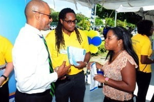 (From left) Rolf Phillips – President and CEO, Consolidated Finance Co. Ltd. and Komi Barrow, Compliance Officer engage a UWI student on career options within the ANSA McAL Group of companies.