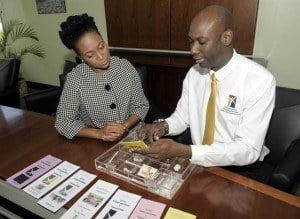 Chairman of Drug Education and Counselling Services (DECS), Pastor Roger Husbands (right) shares with Senior Trust Officer, Wealth Management, CIBC First Caribbean, Nicole Weekes on the DECS' education programmes. The bank donated a multimedia projector the organisation for use in its classes and community outreach.