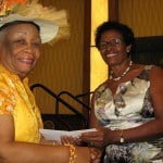 Dame Maizie smiling receives prize from Mrs Bushell
