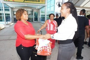 "Digicel Group Diaspora Online Top Up Executive, Alicia Simpson, greets ""Triple the Love"" promotion winner, Shereese Field and her mother, at the Norman Manley International airport in Kingston, Jamaica"