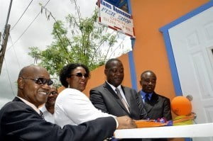 Minister of Industry, International Business, Commerce and Small Business Development, The Hon. Donville Inniss, M.P. (second from right) cutting the ribbon to officially re-open KAMS Aquarium Fish Shop while Leader of the Opposition, The Hon. Mia Mottley (third from right), Senator, The Hon. Patrick Todd (second from left), Cedric Murrell, Chairman of the Board of Directors of the National Initiative for Service Excellence (NISE) Inc. (Ag) (far left) and Owner of KAMS Aquarium Fish Shop, Kevin Murrell (far right) look on.