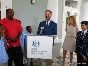 Greg Evans, at podium, expressing delight at assisting Barbadian primary schools in the pursuit of sport