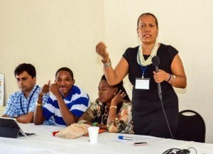 Co-founder of the Global Leadership Coalition, Mary Symmonds, addressing the participants at the opening of the Caribbean Young Leaders EntrepreneurshipBoot Camp. Also seated at the head table are (left to right) Co-founder ofA Million for A Billion (1M1B), Manav Subodh; Global Youth Ambassador and CEO and Co-Founder of Nanostar AMP Group Incorporated, Hashim Ruan; and guest speaker Lynette Eastmond.