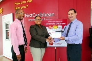 "David Scott, Customer Care Officer, Warrens Banking Centre (left); Bianca Duguid-Smith, Manager, Credit Cards; and sweepstakes winner Mark Goodridge (right) during the presentation ceremony for CIBC FirstCaribbean's ""Give More, Get More"" promotion at the Warrens Banking Centre."