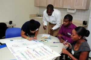 Kris Cadogan (third from left) wants to put the theory he's learned at UWI into practice during his stint with Consolidated Finance. Here he works on a poster as part of a group activity.