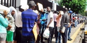 """(IMAGE VIA - El Dia) The Danilo Medina regimegave a 45-day grace period that runs through 1 August 2015, to allow those who have applied to the program to complete their paperwork. """"Despite the hot sun, the line of Haitians spread around the headquarters of the Ministry of Interior and Police"""" Please note the wording used, very prejudicial!"""