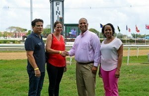 Jason Sambrano of Pinnacle Feeds (second right) presented Monique Archer of the HORSE Charity with monthly feed for the rescued horses the charity cares for at a recent race day at the Garrison Savannah. Looking on are Nicholas Mouttet, the horse owner who conceptualized the partnership, and  Rosette Peirce of the Barbados Turf Club which will give the Pinnacle a complimentary ad in its Race Day programmes for a year.