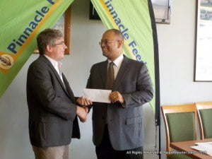 Barbados Turf Club Director Kevin Burke (left, no tie) receives the sponsorship cheque from Managing Dir. of Pinnacle Feeds, Jason Sambrano