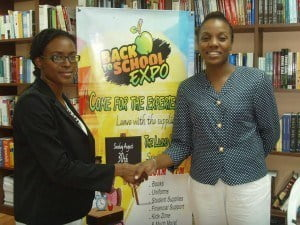 From left Erica Hinkson, Marketing Associate, Chattel House Books and Charlene Alexander, Event Coordinator, Back to School Expo shaking hands in partnership.  In the middle a Back to School Expo poster