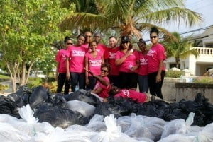 2. Digicel staff members at the beach clean-up recently to help rid the Welches Beach in Christ Church of some of the Sargassum seaweed overtaking local beaches.