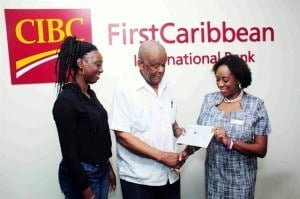 Thomas Watts of Prison Fellowship Barbados receives funds for the fellowship's outreach to children and families of inmates from CIBC FirstCaribbean's Paige Bryan, Manager, Retail Banking Channels while Beverly Bratcher looks on.