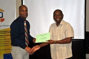Workshop facilitator Kirk Brown (left) presents Director of Research at the Barbados Community College, Dr. Samuel Miller with his certificate of participation in the technical proposal writing training workshop, organised as part of Government's Human Resource Development (HRD) Strategy.