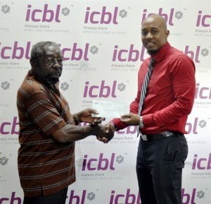 Corporate Communications Specialist with ICBL, Randy Howard (right), presenting the cheque to Special Olympics Barbados Treasurer, Cecil Collymore.