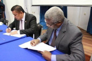 Edward Greene, Division Chief, Technical Cooperation Division of the Caribbean Development Bank signs agreement with Minister of Trade and Industry, Don Soejit Tosendjojo