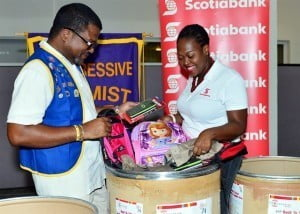 President of the Progressive Optimists Club, Cameron Sobers (left) and Scotiabank Marketing Manager Amanda Lynch-Foster (right) take a look through some of the school supplies donated by staff and customers of the bank for the club's Back to School Uniforms & Supplies Drive.