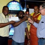 Lucky winner Corey Marshall (second from right) is toasted and congratulated by Lawrence Charles, General Manager of the Bagatelle Complex, Paul Johnson CEO of Paul's Enterprises Limited, and Antoinette Taylor, Assistant Manager at Bagatelle.