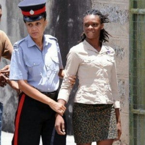 Shakira Nikita Mascoll, 26, of Ashby Alley, Nelson Street was arrested Monday after police executed a search warrant of her home and discovered the weapon along with 29 rounds of ammunition, she faced time on both for not having the requisite licences to do so...Shakira Mascoll being escorted by a police officer. (IMAGE VIA - Xtra Vision Photography, COURTESY: NationNews.com)