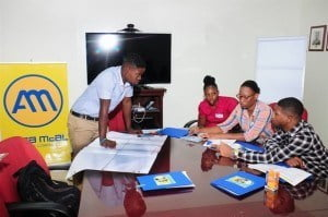Kristie Francis (second from right) spent part of this summer as an intern in the inaugural ANSA McAL (Barbados) Internship Programme. Here she works with group members on a poster during the orientation session.