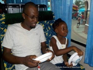 CLICK FOR BIGGER: Father & Daughter gaming on an air conditioned bus!