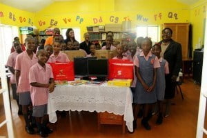 Welches Primary principal Patricia Lovell (right) and students gather in the school's library with the books and equipment donated by Scotiabank's employee action team from its Corporate and Commercial Banking Centre.