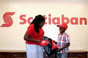 Kiddy Cricket 15th Anniversary Grant Winner Jaden Webster (left) smiling broadly as he receives his backpack of supplies from Scotiabank marketing manager Amanda Lynch-Foster.