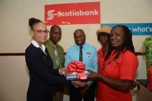 Personal Banking Officer at Scotiabank's Broad Street branch, Receda Clarke (left) hands over school stationery and supplies to representatives from the Family Care Support Group of the HIV Food Bank.