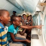 Some of the Junior Monarch contestants looking through their porthole in excitement