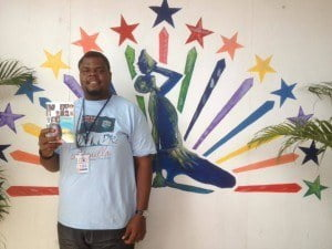 Lexus Ryan with copy of Where I See The Sun – Contemporary Poetry in Anguilla in which his poetry appears. Logo of CARIFESTA XII is in background, Haiti, 2015. (© LP photo)