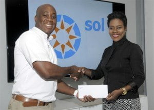 SOL's General Manager Ezra Prescod hands over the cheque to Elisha Stuart as he gets final details on the walk from her.