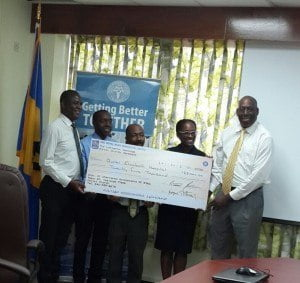 Executive director of ICAB Reginald Farley presenting the cheque for $25 000 to CEO of the QEH while Roger Arthur - Immediate Past President, Treasurer Reuben Blenman and President Lisa Padmore look on.